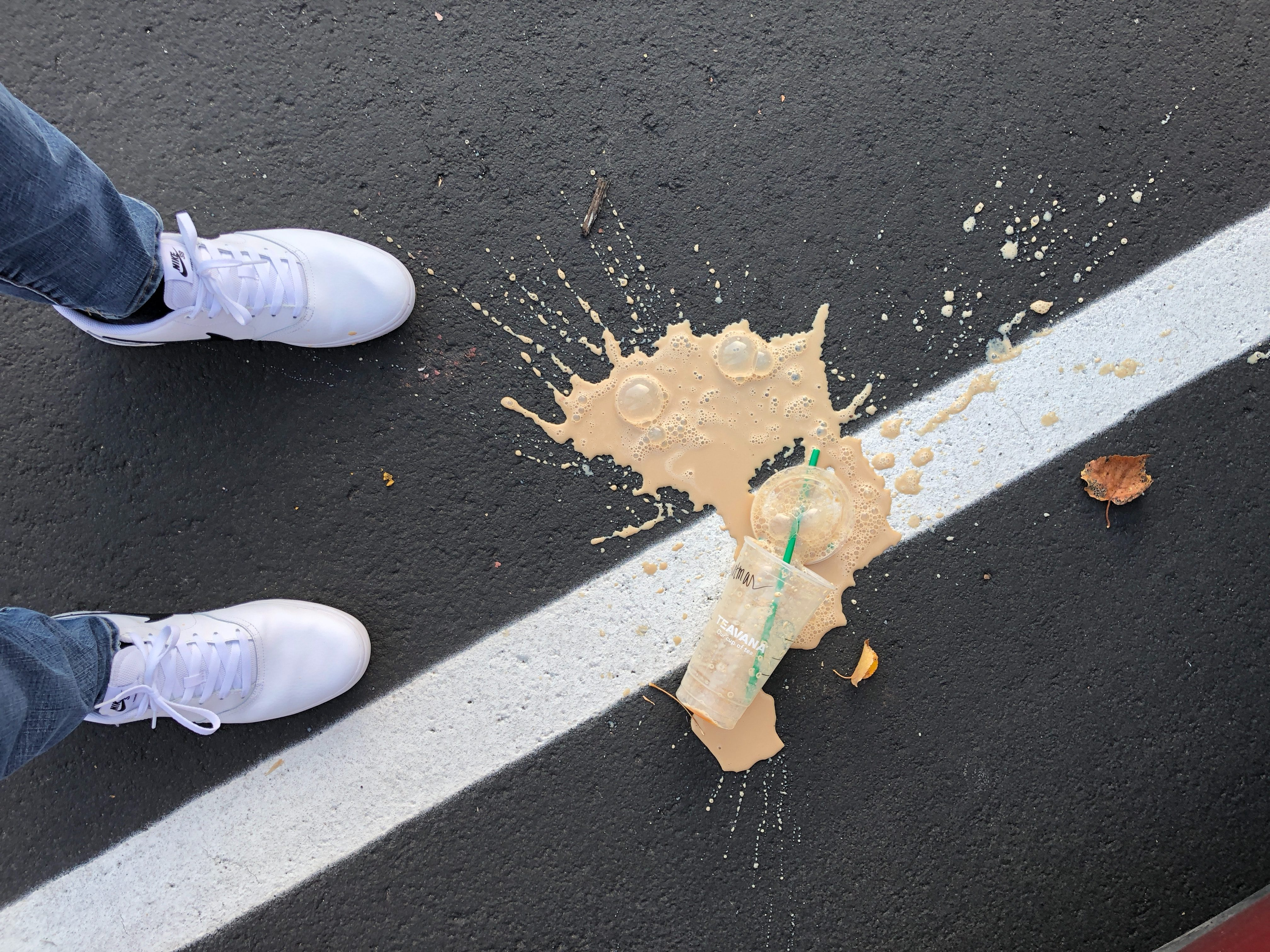 Coffee spilled on the ground in a parking lot by viewer's feet.